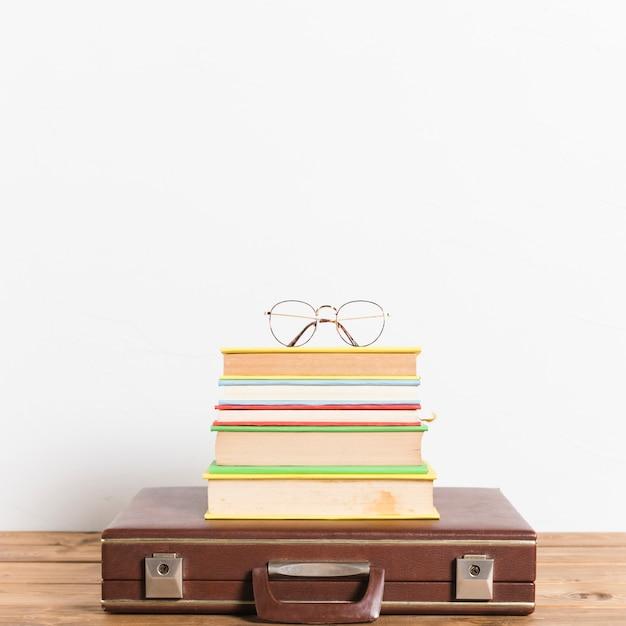 Lunettes classiques sur une pile de livres sur une valise vintage Photo gratuit