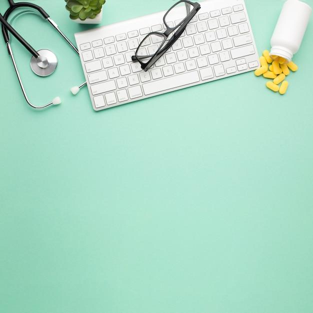 Les lunettes sur le clavier sans fil près des pilules ont renversé la bouteille avant et le stéthoscope sur une surface verte Photo gratuit