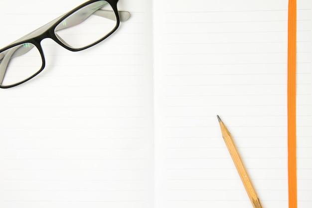Lunettes et crayon brun sur le cahier de travail. vue de dessus, concept plat laïque. Photo Premium