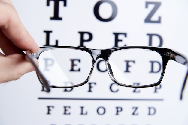 Des lunettes dans les mains sur le fond de la table pour la vision. Photo Premium