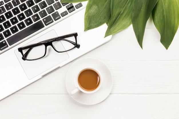 Lunettes noires et feuilles sur un ordinateur portable ouvert avec une tasse de café sur le bureau en bois Photo gratuit
