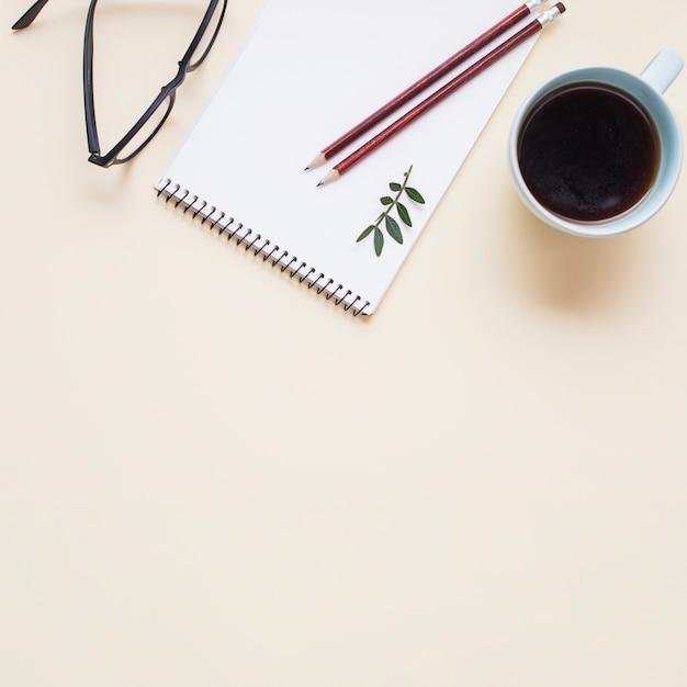 Lunettes noires; tasse à thé et deux crayons sur le bloc-notes en spirale sur fond beige Photo gratuit