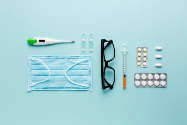 Lunettes et pilules sur un ordinateur portable près du stéthoscope sur une surface bleue Photo gratuit