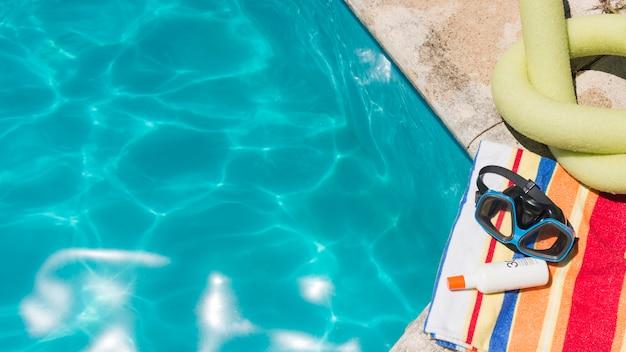 Lunettes de protection avec une lotion sur une serviette près du jouet et de la piscine Photo gratuit