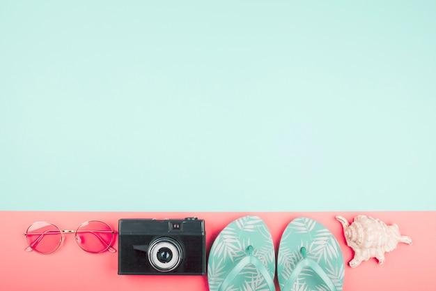 Des lunettes de soleil; caméra; tongs; conque sur fond corail et menthe Photo gratuit