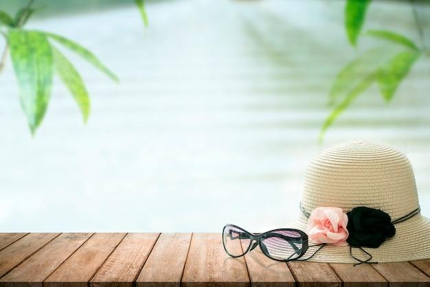 Lunettes de soleil et chapeau de paille sur la table en bois avec fond de nature Photo Premium