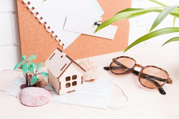 Lunettes De Soleil, Coquillages, Petit Palmier, Masque Facial, Petite Maison En Bois Sur Le Bureau, Panneau De Liège En Arrière-plan Photo Premium
