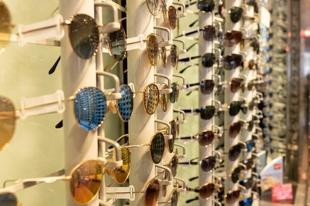 Lunettes de soleil de couleurs différentes dans un présentoir pour lunettes dans un optique Photo Premium