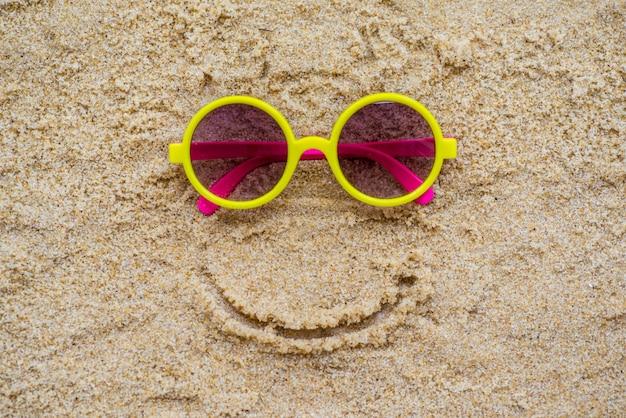 Lunettes de soleil dans le sable à la plage Photo Premium