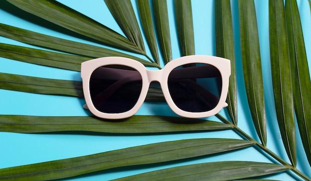 Lunettes De Soleil Sur Les Feuilles De Palmiers Tropicaux Sur Fond Bleu. Vue De Dessus Photo Premium