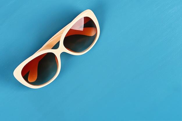 Lunettes de soleil sur un fond bleu. vue de dessus. fond d'été. Photo Premium