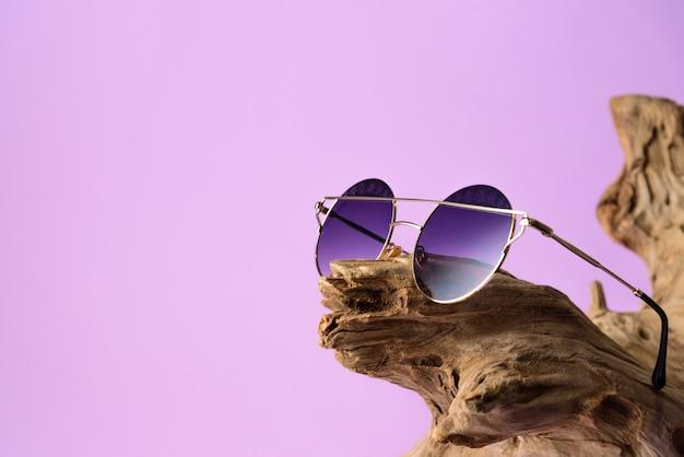 Lunettes de soleil à la mode avec des lentilles violettes placées sur du bois. sur fond violet Photo Premium