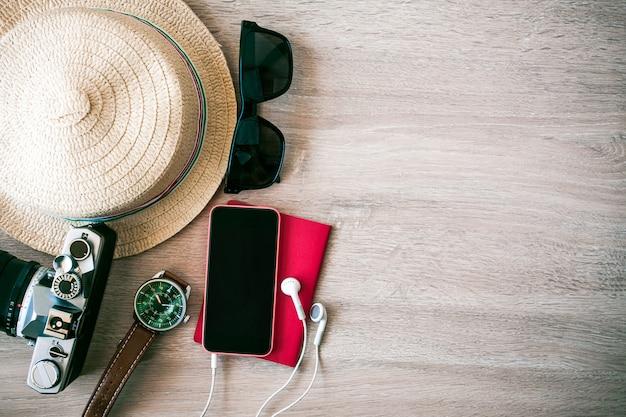 Lunettes de soleil, téléphones-appareils photo, casquettes, passeports mettez du parquet pour préparer le week-end. Photo Premium