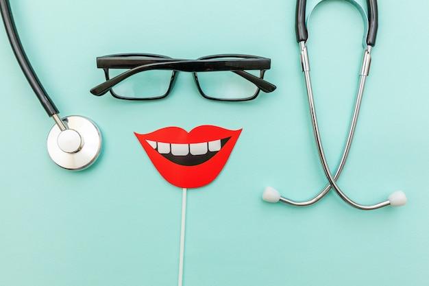 Lunettes de stéthoscope équipement de médecine signe de sourire dents isolé sur tendance bleu pastel Photo Premium