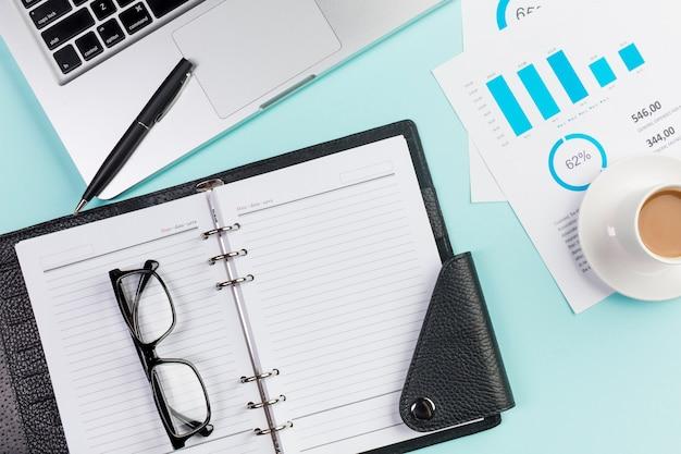 Lunettes de vue sur agenda, ordinateur portable, stylo, tasse à café et plan budgétaire sur le bureau Photo gratuit