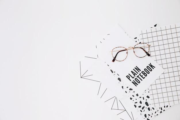 Lunettes de vue sur cahier simple et pages sur fond blanc Photo gratuit