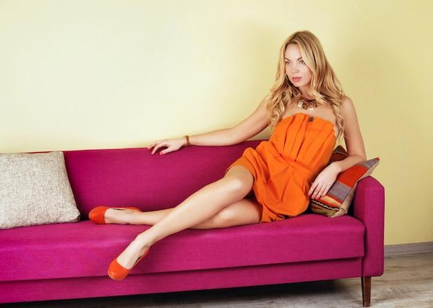 Luxueuse Femme Blonde Dans Une Robe Orange Sur Canapé Violet Photo Premium