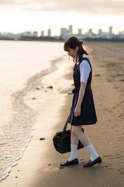 Lycéen Femelle Asiatique Marchant Sur La Plage Photo Premium