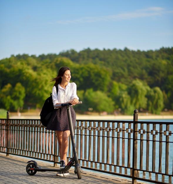 Lycéenne teen conduisant son scooter électrique près du lac Photo Premium