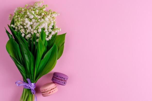 Lys De La Vallée Noués Avec Un Ruban Violet Et Des Macarons Sur Un Bleu Pastel. Photo Premium