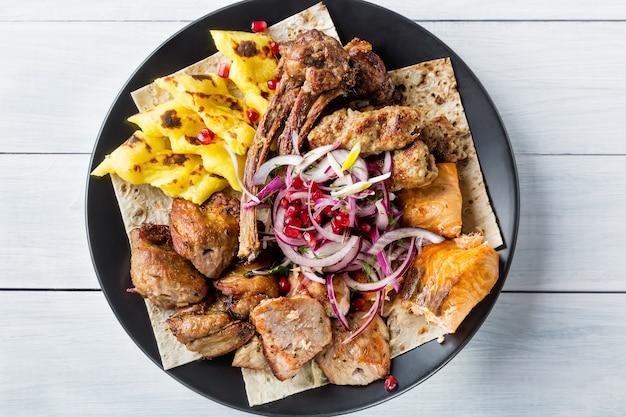 Lyulya kebab, shish kebab, poisson de saumon grillé, grains d'oignon et de grenade sur plaque noire et table en bois blanc Photo Premium