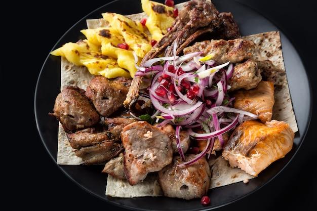 Lyulya kebab, shish kebab, poisson de saumon grillé, grains d'oignon et de grenade sur plaque noire Photo Premium
