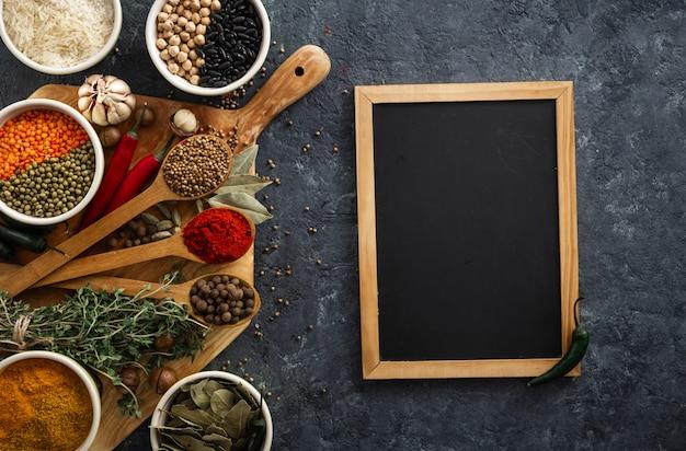 M e n u . tableau avec épices et herbes vue de dessus avec riz, haricots divers sur fond sombre Photo Premium