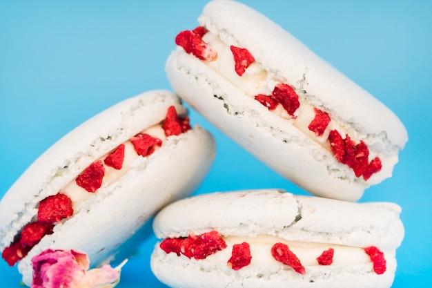 Macaron blanc délicieux avec des fleurs sur fond bleu Photo gratuit