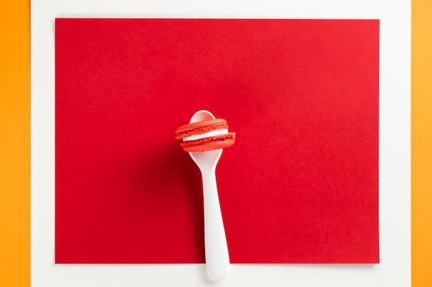 Macaron dans une cuillère avec un fond rouge Photo gratuit