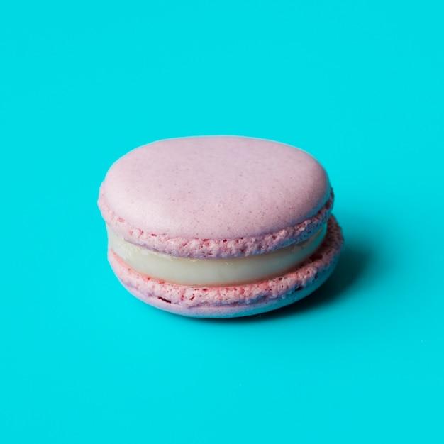 Macaron rose à la crème sur fond bleu Photo gratuit