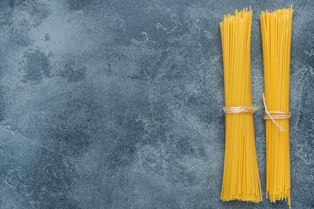 Macaronis crus, spaghettis sur une table en pierre sombre avec espace de copie. pâtes italiennes faites maison. Photo Premium