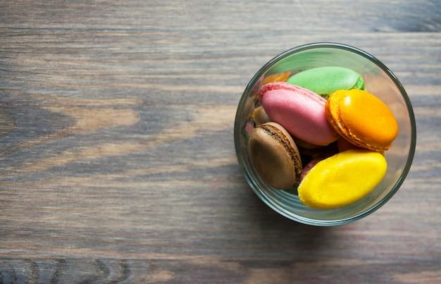 Macaronis multicolores dessert français sur une table en bois brune Photo Premium