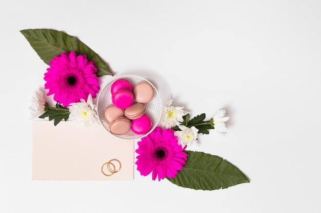 Macarons sur assiette entre fleurs, feuillage, papier et cernes Photo gratuit