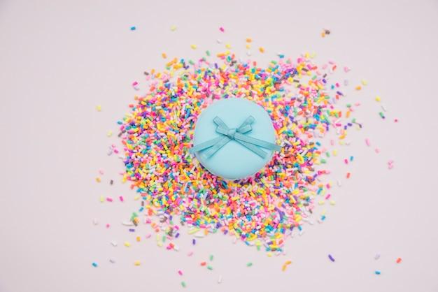 Macarons bleus sur les arrosages colorés sur fond coloré Photo gratuit