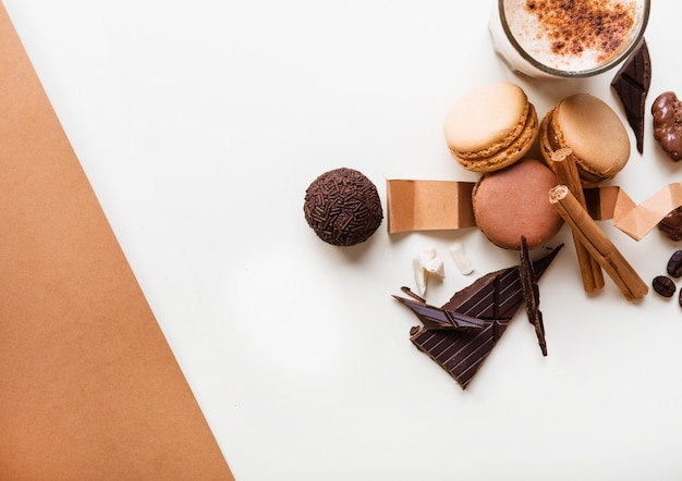 Macarons; boule de chocolat et verre de café avec des ingrédients sur fond blanc Photo gratuit