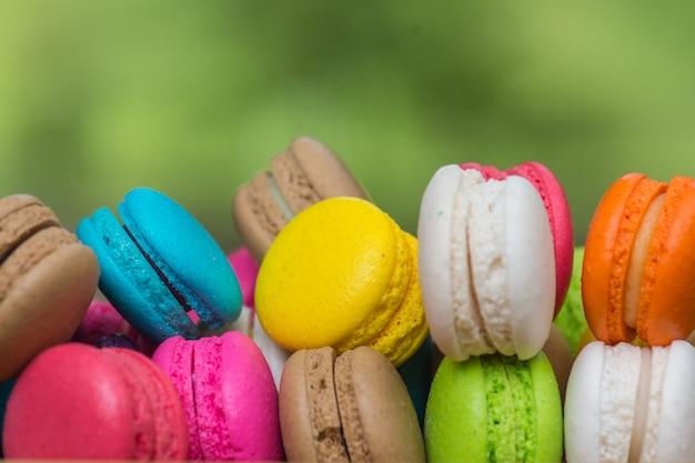 Macarons colorés dans un plat sur une table en bois Photo Premium