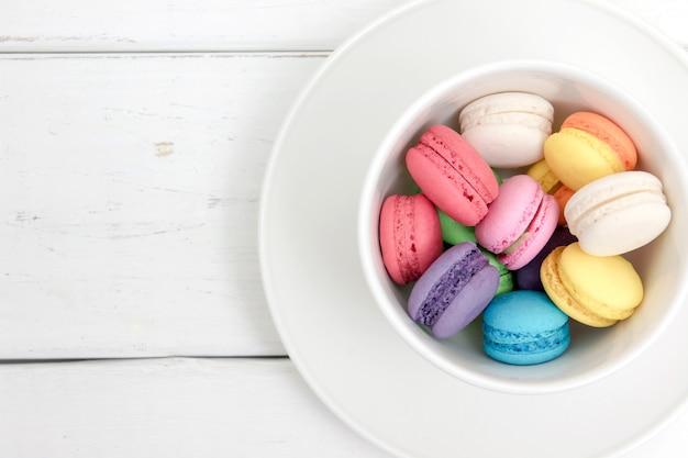 Macarons colorés dans une tasse avec pastel vintage filtré Photo Premium