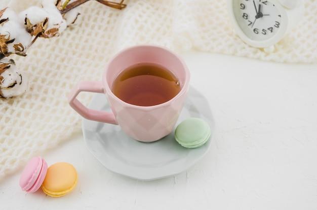 Macarons colorés avec du thé vert à base de plantes dans une tasse en céramique rose et une soucoupe sur le bureau Photo gratuit
