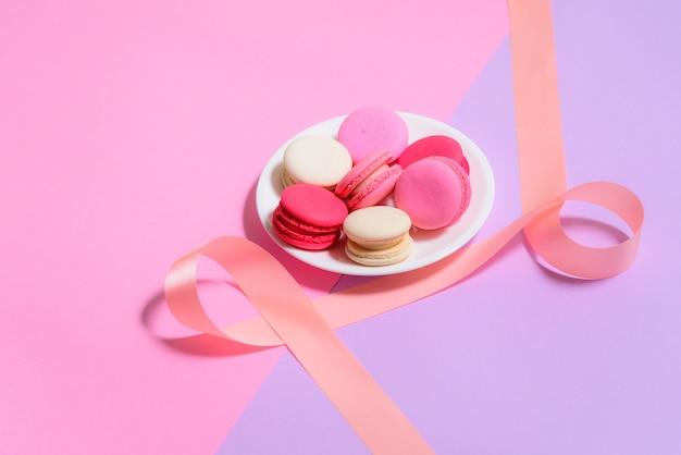 Macarons colorés faits maison ou macaron sur une plaque blanche sur fond rose et violet Photo Premium