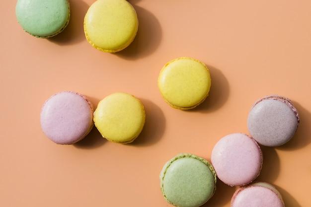 Macarons colorés sur fond coloré Photo gratuit