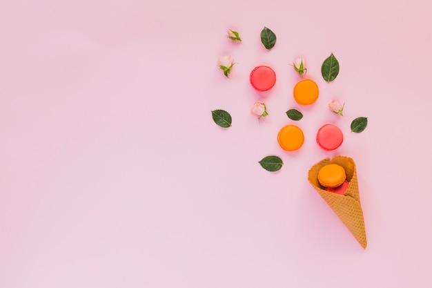 Macarons colorés; rose; et feuilles disposées sur le cône de gaufre sur fond rose Photo gratuit