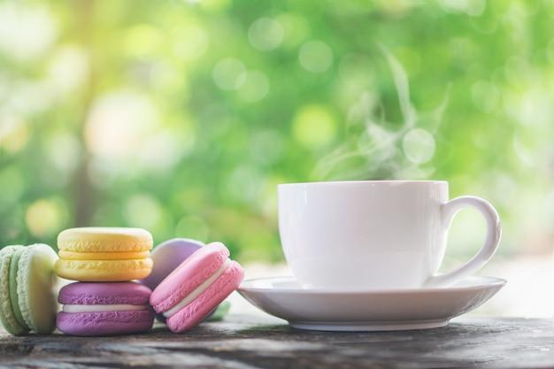 Macarons colorés avec une tasse de café chaud Photo Premium