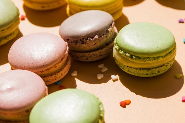 Macarons avec forme de coeur pépite sur fond beige Photo gratuit