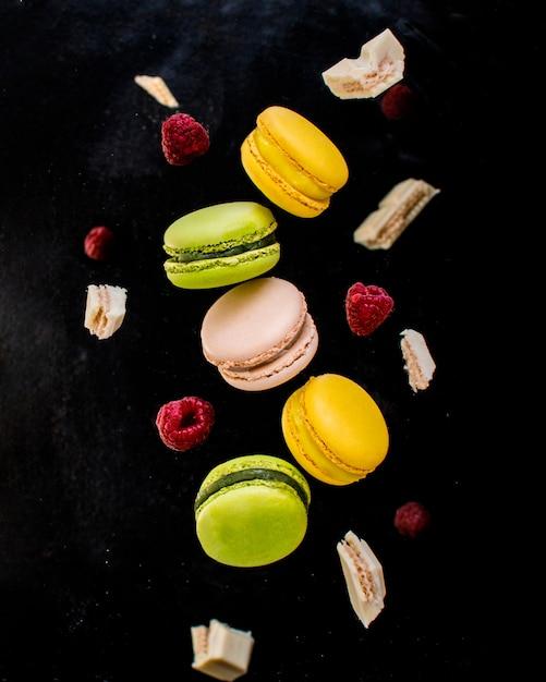 Macarons français colorés en mouvement avec chocolat blanc et framboises Photo Premium