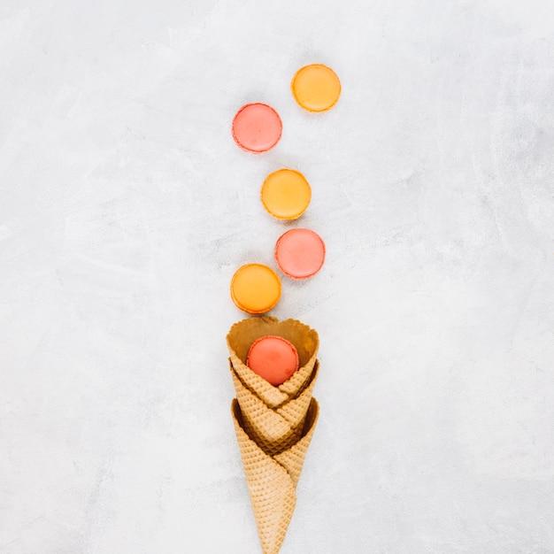 Macarons près des cônes de gaufre Photo gratuit