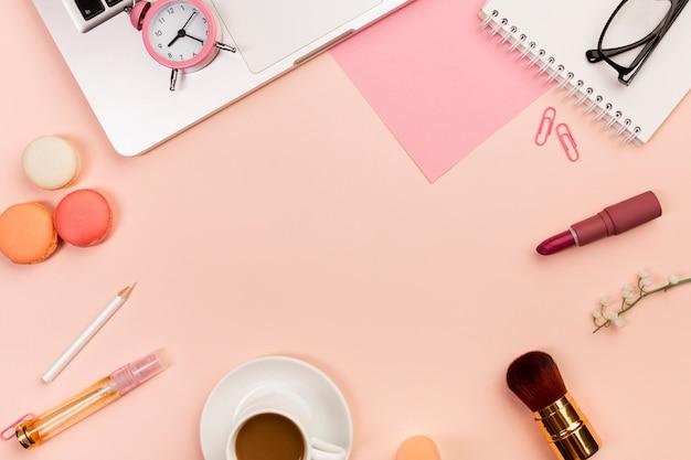 Macarons, tasse à café, pinceaux de maquillage, réveil, ordinateur portable sur fond couleur pêche Photo gratuit