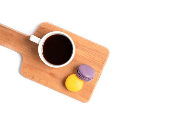 Macarons et une tasse de café sur une planche de bois Photo Premium