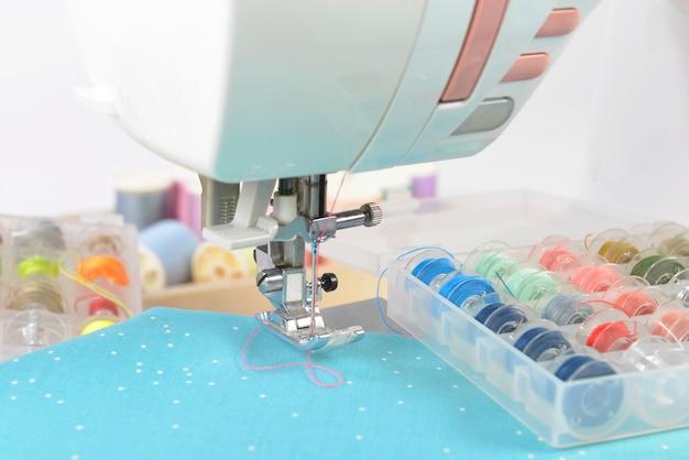 Machine à coudre et rouleaux de fils colorés, ciseaux, tissus et accessoires pour la couture. Photo Premium