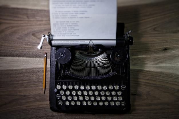 Machine à écrire et un crayon sur la table mezzanine Photo Premium