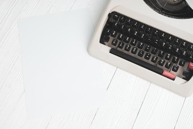 Machine à écrire rétro avec une feuille de papier vierge sur une table en bois blanc. Photo Premium